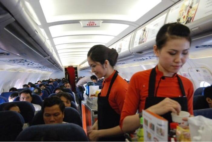 Các tiếp viên hàng không Jetstar sử dụng áo dài cách điệu kết hợp với tạp dề đen khi phục vụ khách hàng trên chuyến bay