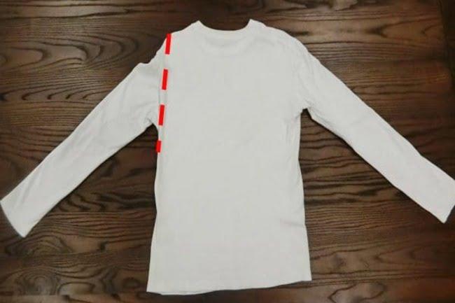 Gấp tay áo bên phía cánh trái vào trong theo đường màu đỏ