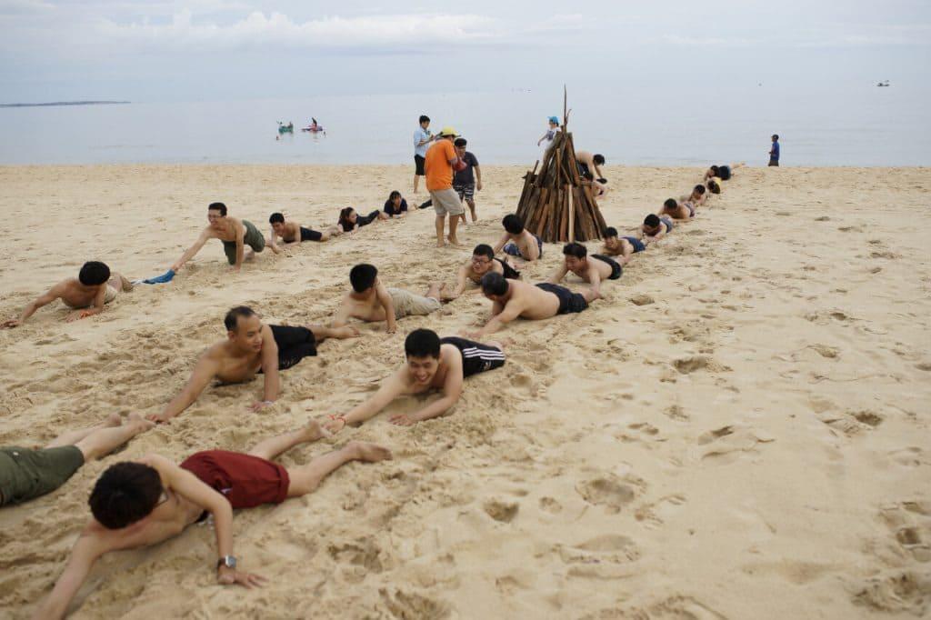 các bạn nam cố gắng giành chiến thắng trong một trò chơi team building ở bãi biển